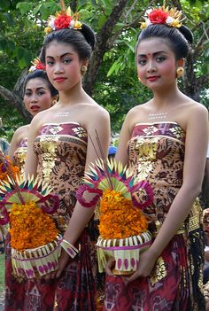 Balinese Women carry temple offerings with woven flowers & wear blossoms in hair