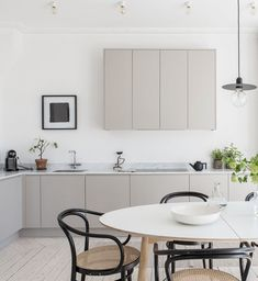 taupe and white kitchen with black and beige accents, pantone warm sand, light tan, black bentwood chairs