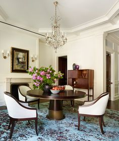 The entry doubles as a formal dining room and is furnished with custom pieces that reflect the elegant lines of the architecture. The custom rug is by Sacco.