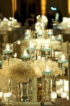 Low white rose arrangements and candle wedding decor.
