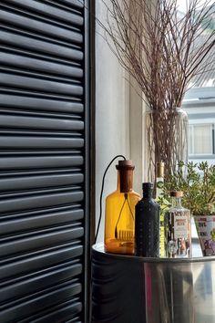 Detalhe | Sobre o tambor cromado da Muui, garrafas de vidro antigas. A marrom é uma luminária da LZ Studio (Foto: Denilson Machado/MCA Estúdio)