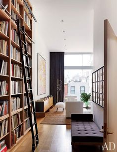 Floor-to-ceiling oak bookshelves distinguish the library of a home decorated by D'Apostrophe Design.