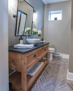 Reclaimed wood vanity made by the Amish topped with honed absolute black granite. Herringbone pattern on the floor tile.