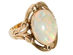 Art Nouveau White Opal Ring. At first glance the sweeping sensual curves so closely associated with the Art Nouveau movement become apparent. The north and south elements of the mounting appear to take the form of human lips enveloping an oval white opal cabochon of 2.8 carats. The kinetic color play of bright orange, lemon lime, peacock blue, electric green and buttercup yellow brings to mind the intensity of a sky full of thunder clouds with a spectacular demonstration of lightning…