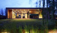 Chalé de madeira, com grandes janelas de vidro do piso ao teto, varanda com mesa de jantar e cadeiras, gramado e toras de lenha decorando a parede. Chalé Contemporâneo em Kapuvár  por Tóth Project Architect Office