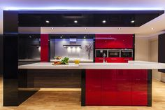 Cocina en rojo y negro, con acabado en brillo. La iluminación y la encimera en blanco aportan luminosidad al espacio. Una cocina elegante y atrevida.