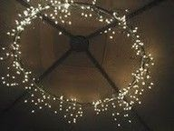 High ceiling? Make your own decorative lights with a hula hoop and icicle lights. Elegant and cheap meet at last.