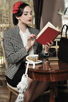 Idda van Munster reading in a cafe. Van Munster is a Bosnian vintage girl and model. She admires old Hollywood and is a lover of all things ...