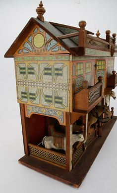 """Large Bliss Stable: The roof has 2 dormer windows and is surmounted by an imposing cupola (paper replaced as noted by Mrs. Jacobs).This example is offered with livestock as pictured and described on page 362-363 of Antique Dolls' Houses, Flora Gill Jacobs © 2005. Included with the stable is a scarce diminutive curry comb as seen in the aforementioned book.  25.75"""" t. x 23.25"""" l."""