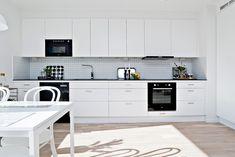 Ljust kök från Ballingslöv med svart bänkskiva, släta vita skåpluckor och vitt stänkskydd. LOCATION: Etagelägenhet i Luleå