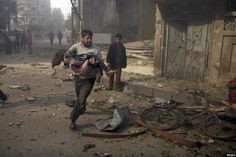 A man carries an injured girl as he rushes away from a site hit by what activists said were air strikes by forces loyal to Syria's president, in the Douma neighborhood of Damascus. (Reuters/Bassam Khabieh)