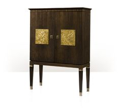 A mahogany and fumed figured Eucalyptus veneered bar cabinet, the rectangular top above two doors with Art Deco gilt relief inset panels, opening to reveal an interior of glass holders above an underlit frosted glass surface, six drawers and a fall front leather inlaid cabinet, ion square tapering legs with brass collar details and cappings.