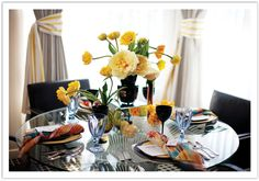 """""""For this modern table design we started with a mirrored cube as a center riser to place a modern inky black vase filled with lush open soft yellow peonies and yellow tulips, courtesy of Isari Flower Studio. We brought in different shades of yellow including dark and light amber and a gorgeous hand-blown glass vase by artist Jess Wainer."""""""