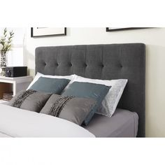 dark grey fabric Headboard connected by grey pillows on the bed
