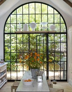 Kitchen with an amazing garden window view. Love the shelf over window too. So pretty!