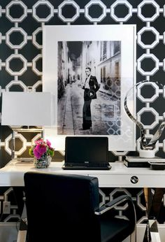 Stunning office design with white & black octagon geometric wallpaper, white lacquer desk, and glass lamps
