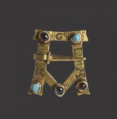 """This private, devotional brooch is shaped like an """"A"""" and inscribed with the abbreviated prayer of AGLA: Atha Gebri Leilan Adonai (""""Thou art mighty forever, O Lord""""). English, 13th century, gold, malachite, sapphire and semiprecious stones"""