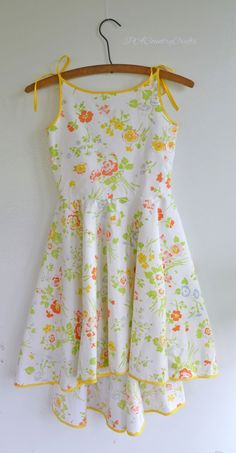 PACountryCrafts: Sunrise Dress Tutorial This is such a pretty 1950s inspired girls Easter dress made from a vintage sheet and bright yellow bias tape. It has a high-low circle skirt and the bodice has a scoop back with buttons.