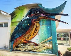 "Artist Arturo ""Bordalo II"" uses materials like old tires, scrap metal, steering wheels, oil paint, and bumpers to form impressive, larger-than-life 3D murals on walls and back alleys throughout the city."