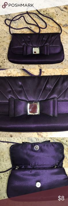 """Purple Evening Clutch/Handbag/Shoulder Bag This Purple Evening Clutch/Handbag/Shoulder Bag features a bow on the front with a mirrored knot. Wear this as a Clutch, or Handbag using the attached chain with 5.5"""" drop or as a Shoulder Bag using the cord with 21"""" drop. Bag measures 9""""x5"""" and is perfect for evening essentials like phone, keys, credit card and lipstick. Used twice and 2 small pulls are only imperfection. Fabric is 100% polyester satin-look. Bags"""