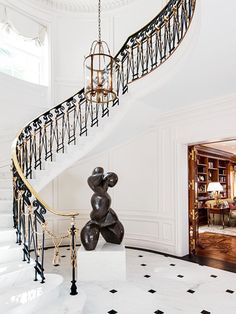 grand tiled staircase with figurative sculpture and black and white tiles // foyers