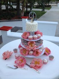 "This small wedding cupcake tower has 40 cupcakes and a top cake.  The cupcakes are strawberry shortcake and the other half are chocolate chip with oreo buttercream. The cupcakes have cupcake wraps from ""Dress My Cupcake"" in coral. This was for a wedding at the Key Largo Lighthouse.  The display uses fresh flowers."
