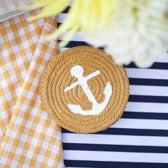 DIY Nautical Coasters   Supplies Cardboard Coaster or Compass Pen Cotton Rope (length depends on number you'd like) Pins Tacky Glue Scissors Acrylic Paint (multiple colors are optional) Paintbrush Tape (optional) A small paper stencil (optional) —> Download the anchor stencil sheet here.