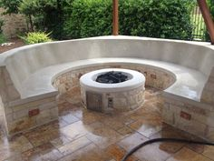 Custom rock gas fire pit with concrete benches and fire ring.
