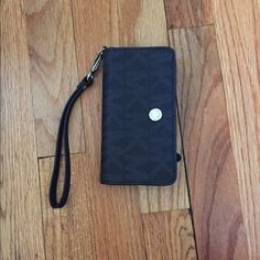 Michael Kors Signature Logo Black Wristlet Used but great condition. No rips, tears, or stains. Holds an iPhone 6 in the left inside pocket. 6 credit card slots on the right, with one more pocket behind credit card slots. Coin compartment on back. Wristlet strap. Silver hardware. Michael Kors Bags Clutches & Wristlets