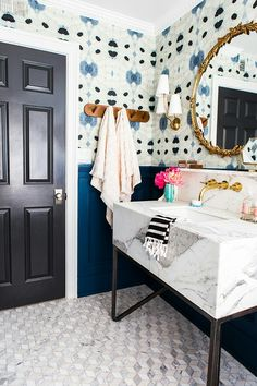 Gorgeous wallpaper and moody blue bathroom with marble and brass accents from The Little Green Notebook