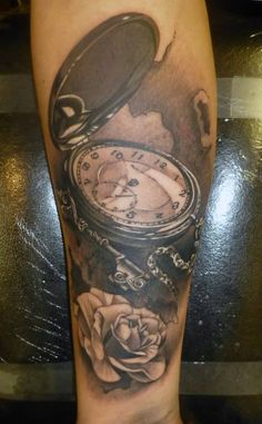 Pocket watch, key and rose tattoo on forearm