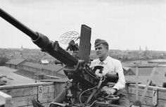 A very sharp image of a German anti-aircraft gunner manning a Czech-made vz.36 20mm Oerlikon gun (based on the Swiss pattern Model 1934). The gun is deployed at the top of a high building or watchtower in the Hague, the capital city of the Netherlands, in 1942. The Oerlikon was widely-deployed and used in many variants by both Axis and Allied forces on land and at sea.