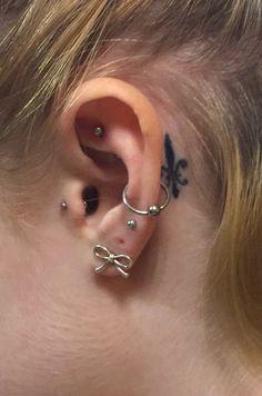 Tragus, double (triple) lobe, rook, orbital, and behind the ear fleur de lis tattoo
