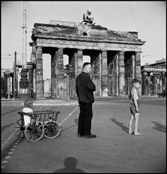 The photo was taken in front of Berlin's historic and very battered Brandenburg Gate separating East and West Berlin during Notice the war-battered structure. Berlin was in ruins because of the. Berlin 1945, West Berlin, Berlin Wall, Berlin Germany, Guernica, Magnum Photos, Magnum Fotografie, Berlin Ick Liebe Dir, Robert Capa