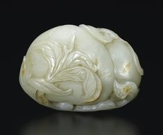 ROLLER CARVED WHITE JADE AND RUST CHINA, QING DYNASTY, QIANLONG PERIOD (1736-1795) A WELL-CARVED WHITE JADE PEACH AND RUSSET GROUP