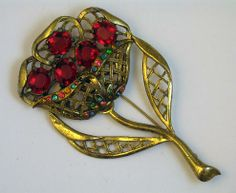 """This gorgeous art deco vintage brooch from Little Nemo features a huge, dimensional flower set with glowing red faceted lucite cabochons and accented with small multi color pastel rhinestones.  The brooch has an open weave design which adds visual interest and keeps it from being too heavy to wear.  The brass setting is in very good condition with great patina and only minimal wear! The brooch is signed LN 50, for Little Nemo and measures 4 by 2 1/2""""."""