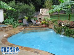 in ground pool with waterfall on retaining wall slope