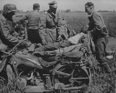 German soldiers loading a wounded man on a motorcycle BMW R11 on the Eastern Front.