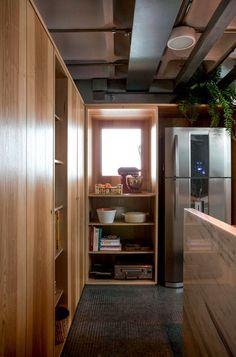 Para criar mais espaço de armazenamento na cozinha, o arquiteto Maicon Antoniolli resolveu integrar uma janela ao restante da marcenaria. Para tanto, criou em torno dela uma caixa de madeira revestida de lâminas naturais em tom de oliveira
