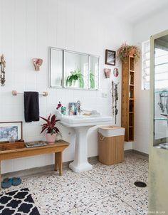 Banheiro com piso de granilite, pia antiguinha e móveis de madeira.