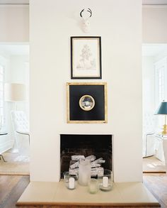A white mantel adorned with framed art by lisa sherry interieurs via Lonny