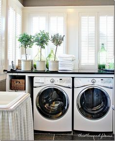 Laundry room ideas from Southern Living idea house - topiaries, glass bottles filled with laundry detergent in a basket