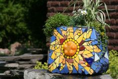 What can you make with a junk toilet tank, a plastic coke bottle, and some broken tiles? A one-of-a-kind mosaic planter for the garden!