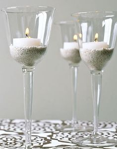 Wine glasses, cheap DIY decor. I like the sand in there, or maybe some glass beads, fill with water and float the candles.