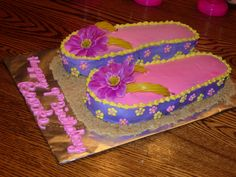 "Flip Flop Cake I made this for Brooke's 9th birthday.  TIPS: Do all the icing and detail work on a separate surface.  Then prep the display board with crushed graham cracker ""sand"". Transfer using a pancake turner.  Then add yellow twizlers for the straps and silk flowers."