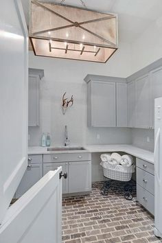 A gray dutch door opens to an exquisite gray cottage laundry room clad in brick floor tiles is equipped with gray shaker cabinets adorning polished nickel cup pulls and a white marble countertop fitted with a large stainless sink and a polished nickel gooseneck faucet fixed in front of gray mini brick backsplash tiles complementing gray upper cabinets.