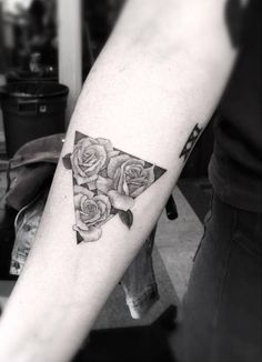 Fine line triangle with three roses on the right inner forearm.