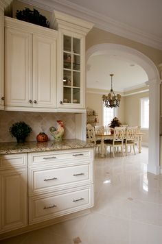 NDA Kitchens - Light granite, light cabinets, archway to dining room, tile