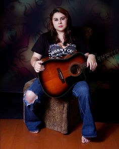 This is a cool photograph of the same high school senior. She's wearing the same Johnny Cash shirt and holding her guitar. She must have been a big fan of his music.