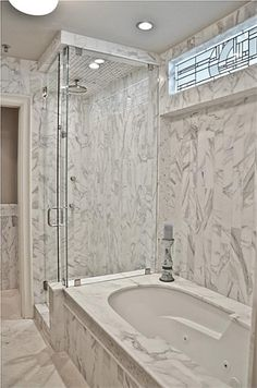 master bath with whirlpool tub surround with slab marble shower also is tiled with marble